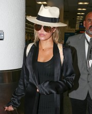 Khloe Kardashian accessorized with a white Panama hat while catching a flight from Miami.