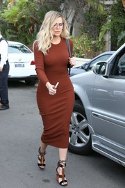 Khloe Kardashian was all curves in a body-con rust sweater dress while headed to a party in Beverly Hills.
