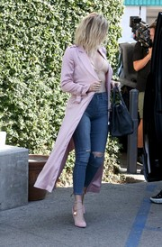 Khloe Kardashian looked perfectly put together, as always, in a pink House of CB trenchcoat, a pair of ripped jeans, and a nude bodysuit while out and about in Studio City.