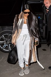 Kim Kardashian was spotted out in New York City wearing light-gray sweatpants under a striped fur coat.