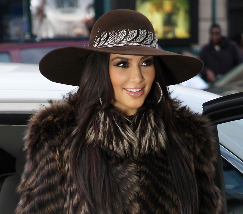 Kim rocks a sueded felt feather hat with her luxurious fur coat. We love  this c3cb2ab7688a
