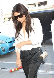 Kim Kardashian styled her airport outfit with a chic Yves Saint Laurent tasseled shoulder bag.