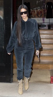 Kim Kardashian looked uncharacteristically conservative in a velour track jacket while shopping in Paris.
