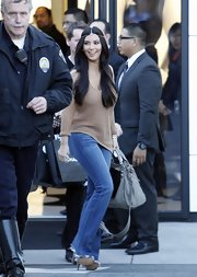 Kim Kardashian embraced the '70s in flared jeans, platforms and an unusual headpiece.