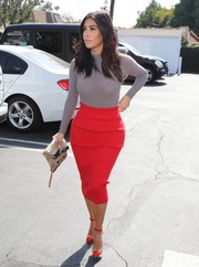 Kim Kardashian teamed her head-turning shopping outfit with a pair of red PVC cap-toe pumps.