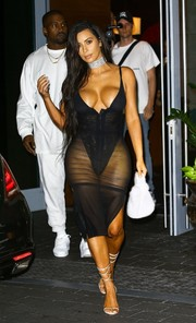 Kim Kardashian ravished in a sheer tight dress layered over a high-cut bodysuit while enjoying a night out in Miami.