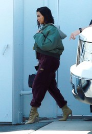 Kim Kardashian dared to go baggy in purple Adidas track pants teamed with a padded bomber jacket for a day out in Calabasas.