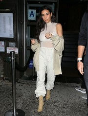 Kim Kardashian sealed off her monochromatic attire with a pair of beige lace-up boots.