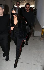 Kim Kardashian punctuated her athletic look with elegant black lace-up boots, also by Yeezy.