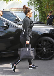 Kim Kardashian doesn't carry just any ol' bag to the gym—she carries this luxurious croc-embossed tote.