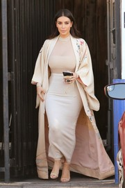 Underneath her robe, Kim Kardashian was curvilicious in a cream-colored pencil skirt and a tight, semi-sheer top.