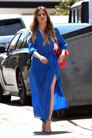 Khloe Kardashian wowed in a cobalt wrap dress teamed with a quilted red bag while filming her reality show.