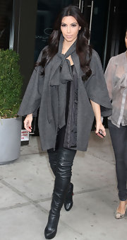 Kim Kardashian kept warm in NYC in a gray wool capelet with an oversize tie front.