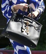 Kourtney Kardashian's black leather purse had a little extra bling with these gold charms.
