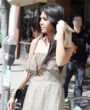 Kourtney Kardashian paired her summer dress with an iconic gold Chanel pendant.