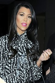Kourtney Kardashian brightened her black and white outfit with a pop of pink on her lips. The look was bold and beautiful.