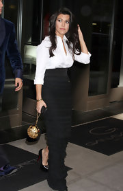 Kourtney Kardashian added flawless shine to her black and white evening attire with a round 24-karat plated Aime clutch.