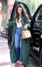 Kourtney Kardashian cut a fashionable figure in a floor-length green trenchcoat by Acne Studios while out in LA.