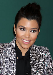 Kourtney Kardashian wore her hair in a casual bun at a book signing for 'Dollhouse.'