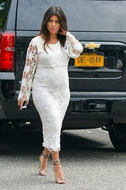 Kourtney Kardashian was demure in a white floral crochet maternity dress while visiting her DASH store.
