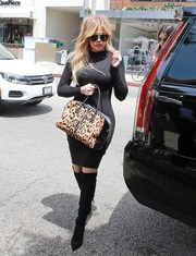 Khloe Kardashian looked very curvy in a black turtleneck sweater dress by Naked Wardrobe while filming her reality show.