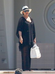 Kris Jenner teamed her top with a pair of sheer, wide-leg pants.