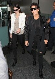 Kendall Jenner spruced up her tattered tee and leggings combo with a white cropped jacket for her flight to LA.