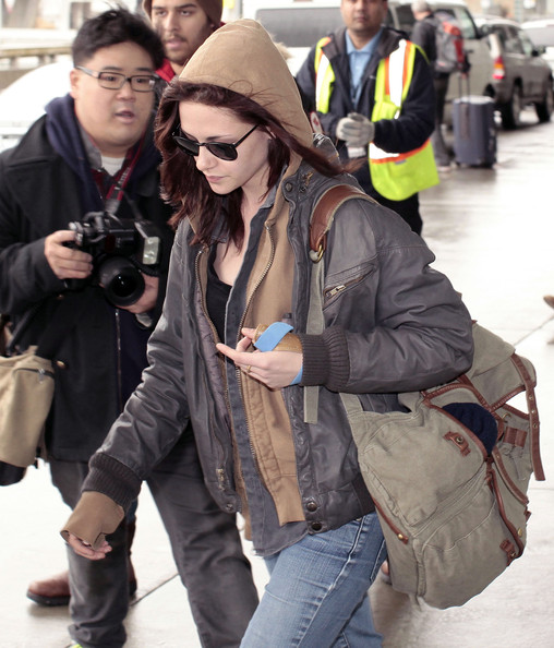 Kristen Stewart made her way through LAX carrying a taupe canvas backpack.