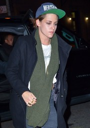 Kristen Stewart stayed cozy with a green knit scarf while enjoying a night out.