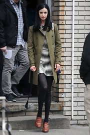 Krysten Ritter looked preppy-chic with this forest green coat paired over a striped mini dress on the set of 'Assistance.'