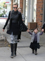 Laeticia rocks a slim fitting leather and wool coat with a unique collar while out with her family.