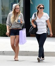 Lauren opted for a comfy shopping look, wearing flip flops with dark denim shorts and a thin leather belt.