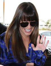 Lea Michele arrived at the airport with her shiny tresses impeccably styled in long sleek layers.