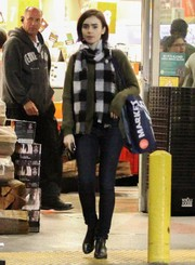 Lily Collins ran errands wearing a pair of skinny jeans and a green sweater.