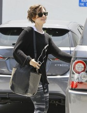 Lily Collins left her gym carrying a stylish studded shoulder bag by Jimmy Choo.
