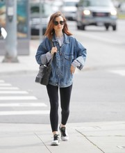 Lily Collins balanced out her baggy jacket with sexy black leggings.