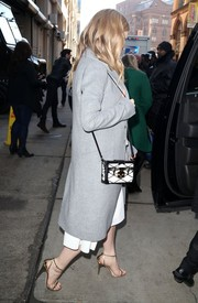 Lily accessorized with a black-and-white lock box purse for her chic winter outing.