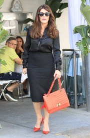 Lisa Vanderpump accessorized with a quilted red-orange bag for an extra pop of color.