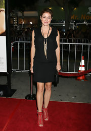 Sasha Alexander added a pop of color to her LBD with red satin cage sandals.