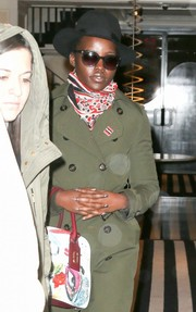 Lupita Nyong'o topped off her look with a black hat.