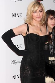 Madonna wears a silver cross pendant and shows off her neckline.