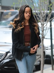 Malia Obama layered a striped brown crop-top under a black zip-up jacket for a day out in New York City.