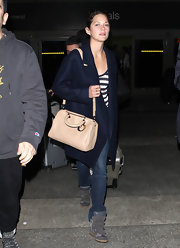 Marion Cotillard lightened up her airport look with a blush bowler bag.