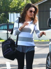 Mila Kunis left her gym carrying a small black duffle with purple trim.