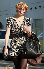 While leaving the salon in LA, Mischa showed off her pinned up curls and floral frock. She added a cute studded leather bag and a matching black belt to pull together the look.