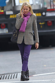 Naomi Watts donned chic purple pants tucked into black leather flat ankle boots.