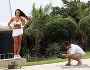 Here, Nicole Bahls poses for the camera wearing a floral bandeau bikini top and white cover-up.