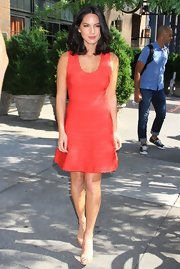 Olivia looked summery and chic in this red day dress that featured a scoop neckline.