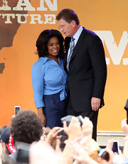 Oprah Winfrey was simple yet stylish in a blue button-down tied at the waist during an event in Melbourne.