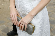 Maria paired her white dress with a crocodile clutch.